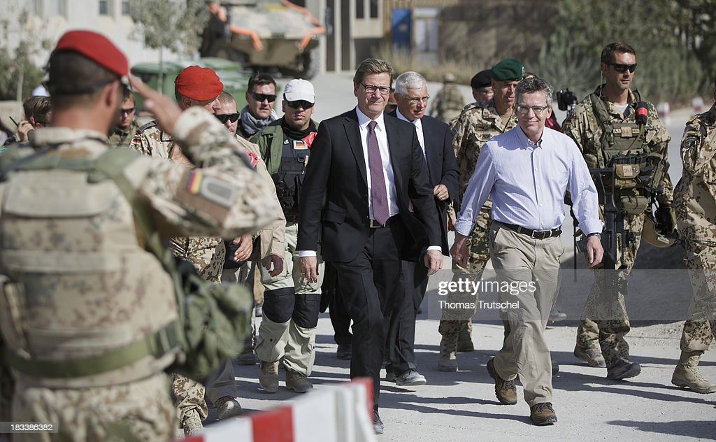 German Foreign Minister <a gi-track='captionPersonalityLinkClicked' href=/galleries/search?phrase=Guido+Westerwelle&family=editorial&specificpeople=208748 ng-click='$event.stopPropagation()'>Guido Westerwelle</a> (L) and German Defence Minister <a gi-track='captionPersonalityLinkClicked' href=/galleries/search?phrase=Thomas+de+Maiziere&family=editorial&specificpeople=618845 ng-click='$event.stopPropagation()'>Thomas de Maiziere</a> are pictured at PRT Kunduz on October 06, 2013 in Kunduz, Afghansitan. Westerwelle and de Maiziere visit Afghanistan to hand over German PRT in Kunduz to the Afghan Military.