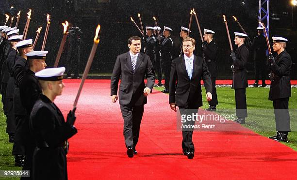 German Foreign Minister Guido Westerwelle and his partner Michael Mronz review an honour guard carrying torches at Bellevue Castle on November 9 2009...