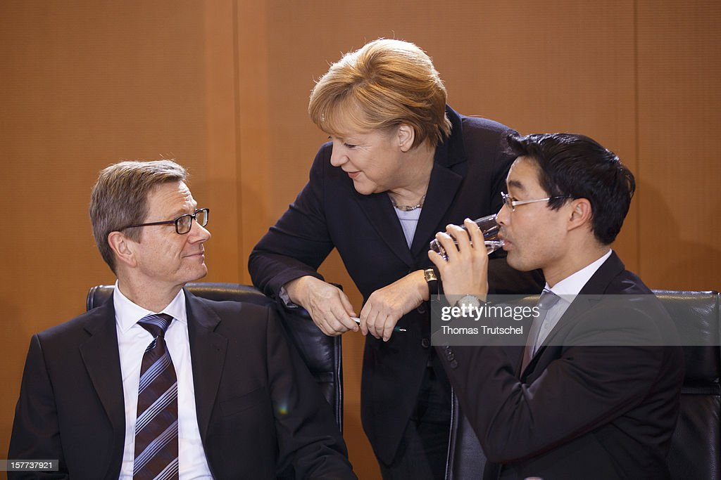 German Foreign Minister <a gi-track='captionPersonalityLinkClicked' href=/galleries/search?phrase=Guido+Westerwelle&family=editorial&specificpeople=208748 ng-click='$event.stopPropagation()'>Guido Westerwelle</a>, German Chancellor <a gi-track='captionPersonalityLinkClicked' href=/galleries/search?phrase=Angela+Merkel&family=editorial&specificpeople=202161 ng-click='$event.stopPropagation()'>Angela Merkel</a> and German Economy Minister and Vice Chancellor <a gi-track='captionPersonalityLinkClicked' href=/galleries/search?phrase=Philipp+Roesler&family=editorial&specificpeople=4838791 ng-click='$event.stopPropagation()'>Philipp Roesler</a> talk prior of the weekly German government cabinet meeting on December 6, 2012 in Berlin, Germany.