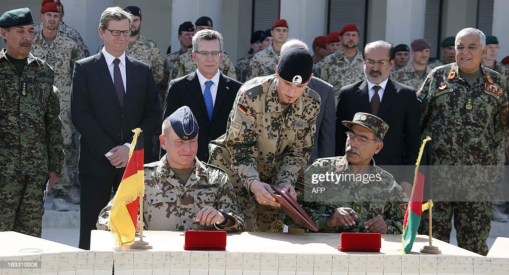 German Foreign Minister Guido Westerwelle (2nd L), German Defence Minister Thomas de Maiziere (3rd L), Afghan Interior Minister Mohammad Omar Daudzai (3rd R, hidden), and Afghan Deputy Defence Minister Enayatullah Nazari (2nd R) watch as German and Afghan Army senior officials sign documents during the handover ceremony of a German base to the Afghan armed forces in Kunduz October 6, 2013. Soldiers of the German contingency of the International Security Assistance Force (ISAF) withdrew from their base in Kunduz and the camp will be used by the Afghan National Army (ANA) and the Afghan National Civil Order Police (ANCOP).