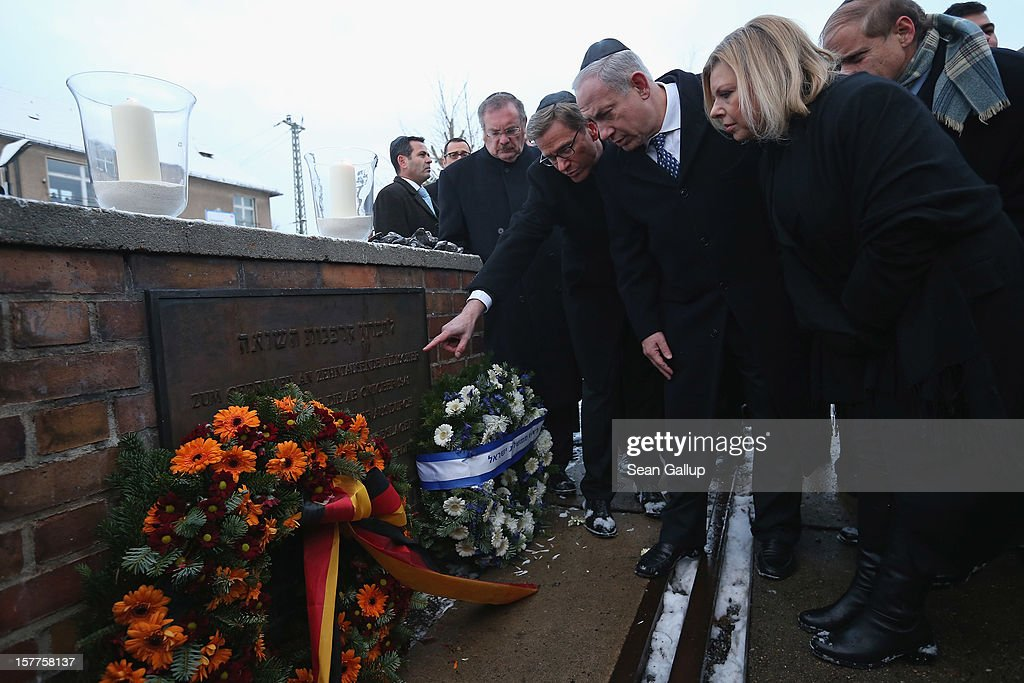 German Foreign Minister Guido Westerwelle points to a memorial as Israeli Prime Minister Benjamin Netanyahu (C) and his wife Sara after they laid candles and wreaths at Track 17, the place where the Nazis deported tens of thousands of Berlin Jews to concentration camps during World War II, on December 6, 2012 in Berlin, Germany. The German and Israeli governments are meeting today in Berlin for German-Israeli government consultations.