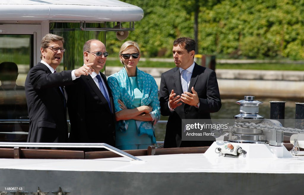 German Foreign Minister <a gi-track='captionPersonalityLinkClicked' href=/galleries/search?phrase=Guido+Westerwelle&family=editorial&specificpeople=208748 ng-click='$event.stopPropagation()'>Guido Westerwelle</a>, Prince Albert II with Princess Charlene of Monaco and <a gi-track='captionPersonalityLinkClicked' href=/galleries/search?phrase=Michael+Mronz&family=editorial&specificpeople=762924 ng-click='$event.stopPropagation()'>Michael Mronz</a> smile during a boat tour on the Spree canal on July 9, 2012 in Berlin, Germany. Prince Albert II and Princess Charlene are visiting Berlin and tomorrow will continue to Stuttgart.