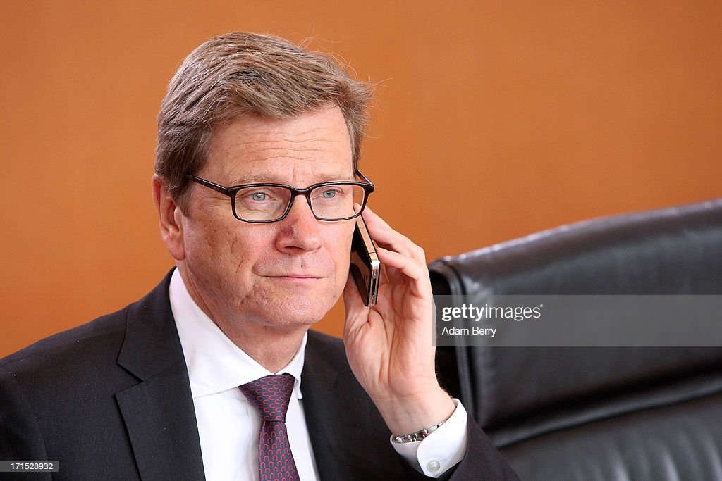 German Foreign Minister Guido Westerwelle speaks on his iPhone as he arrives for the weekly German federal Cabinet meeting on June 26, 2013 in Berlin, Germany. High on the morning's agenda was discussion of the country's 2014 federal budget.