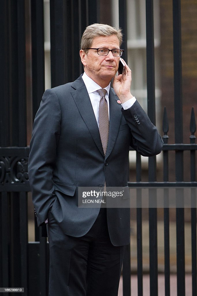 German Foreign Minister Guido Westerwelle talks on a mobile phone as he walks outside Lancaster House during a break in the G8 Foreign Ministers meeting in central London on April 11, 2013. G8 foreign ministers including US Secretary of State John Kerry held a second day of talks in London with the crisis on the Korean peninsula and the Syrian conflict topping the agenda. AFP PHOTO / LEON NEAL