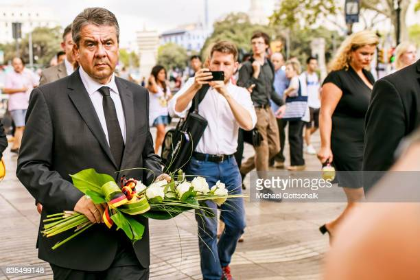 German Foreign Minister Sigmar Gabriel prepares to lay flowers as he visits Las Ramblas near the scene of Thursday's terrorist attack on August 19...