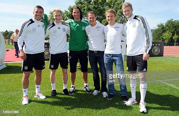 German Formula 1 driver Michael Schumacher and Nico Rosberg pose next to German national football team's players Lukas Podolski Marco Reus and Andre...