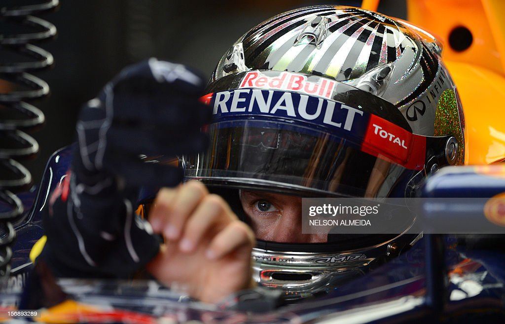 German Formula 1 driver Sebastian Vettel puts on his gloves at the Red Bull pit stop on November 24, 2012 during the free practices at the Interlagos circuit in Sao Paulo, Brazil. AFP PHOTO/Nelson Almeida