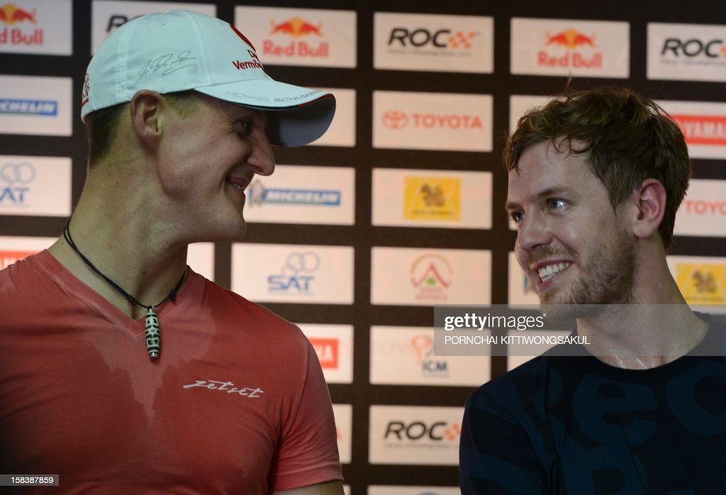 German Formula One driver and seven times World champion Michael Schumacher (L) and German Formula One World Champion Sebastian Vettel (R) talk as they attend a press conference ahead of the annual Race of Champions (ROC) at Rajamangala Stadium in Bangkok on December 15, 2012. The Race of Champions (ROC) will take place in Thailand between December 14 and 16 and brings together heavyweights from all motor racing disciplines in the same type of car.