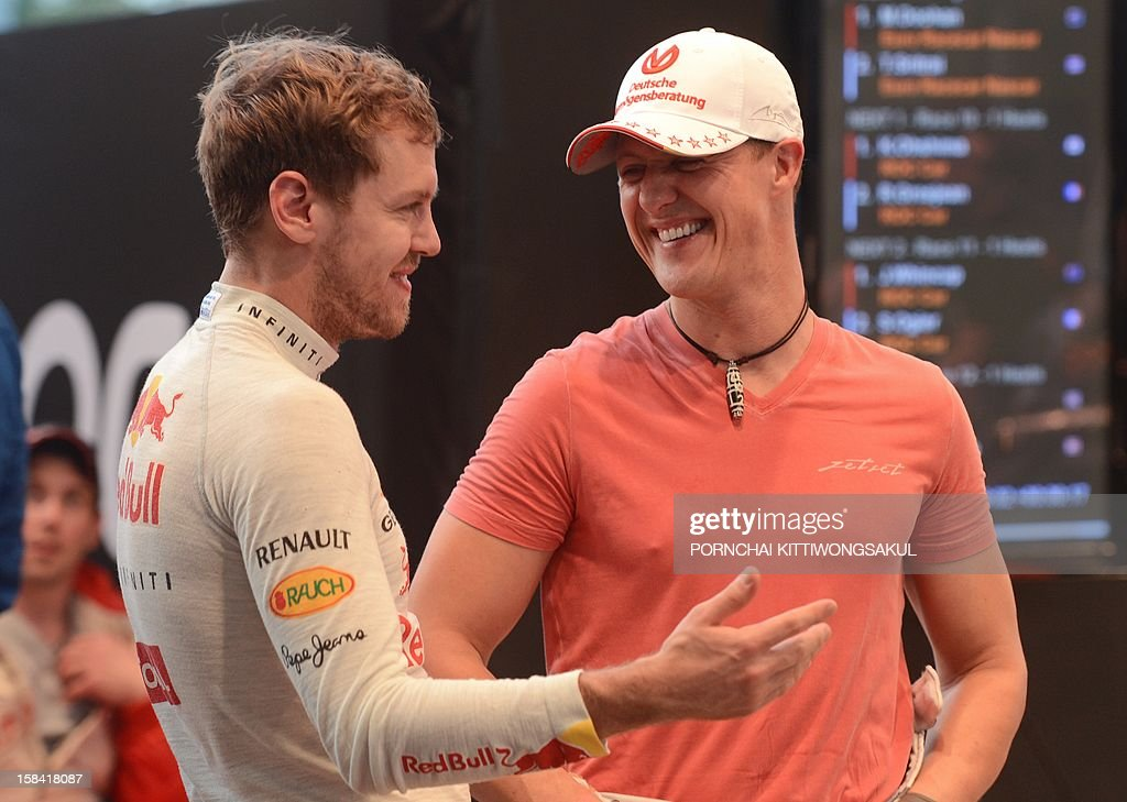 German Formula One driver and seven times world champion Michael Schumacher (R) talks with Formula One world champion Sebastian Vettel (L) during a warm-up for the Race of Champions (ROC) at Rajamangala Stadium in Bangkok on December 16, 2012. The Race of Champions (ROC) will take place in Thailand between December 14 and 16 and brings together heavyweights from all motor racing disciplines in the same type of car.