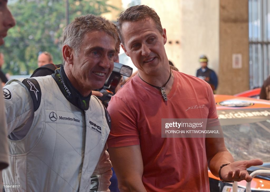 German Formula One driver and seven times world champion Michael Schumacher (R) talks with former Grand Prix motorcycle road racing world champion, Michael Doohan of Australia (L) during warm-up for the Race of Champions (ROC) at Rajamangala Stadium in Bangkok on December 16, 2012. The Race of Champions (ROC) will take place in Thailand between December 14 and 16 and brings together heavyweights from all motor racing disciplines in the same type of car.