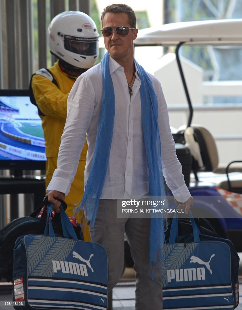 German Formula One driver and seven times world champion Michael Schumacher arrives prior to a warm-up for the Race of Champions (ROC) at Rajamangala Stadium in Bangkok on December 16, 2012. The Race of Champions (ROC) will take place in Thailand between December 14 and 16 and brings together heavyweights from all motor racing disciplines in the same type of car.