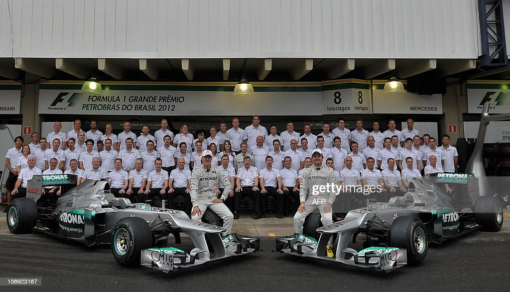 German Formula One driver Michael Schumacher (R) and Nico Rosberg pose with the Mercedes team in the pits on November 25, 2012 at the Interlagos speedway in Sao Paulo, Brazil. Schumacher will retire from the F-1 after the Brazilain frand prix. AFP PHOTO / YASUYOSHI CHIBA / POOL