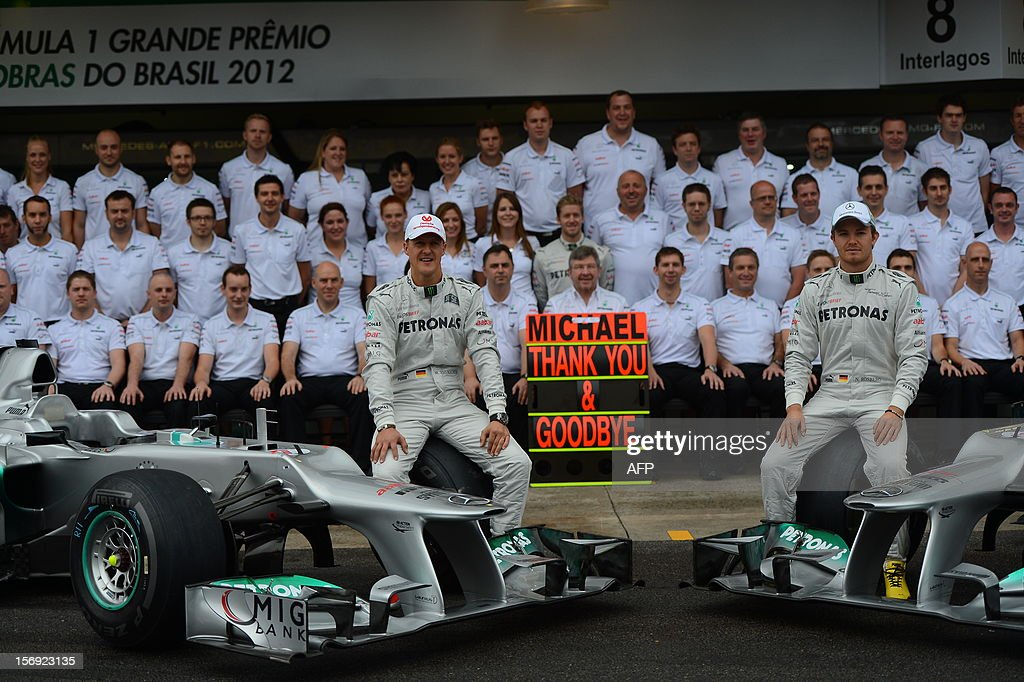 German Formula One driver Michael Schumacher(L) and teammate Nico Rosberg pose with the Mercedes team in the pits on November 25, 2012 at the Interlagos speedway in Sao Paulo, Brazil. Schumacher will retire from the F-1 after the Brazilain frand prix. AFP PHOTO / YASUYOSHI