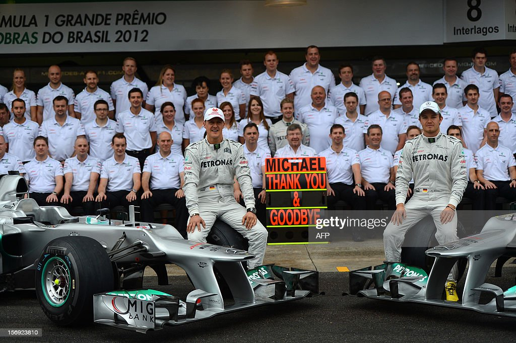 German Formula One driver Michael Schumacher (L) and teammate Nico Rosemberg pose with the Mercedes team in the pits on November 25 , 2012 at the Interlagos racetrack in Sao Paulo, Brazil. Michael Schumacher will retire from the F-1 after the Brazilian GP.