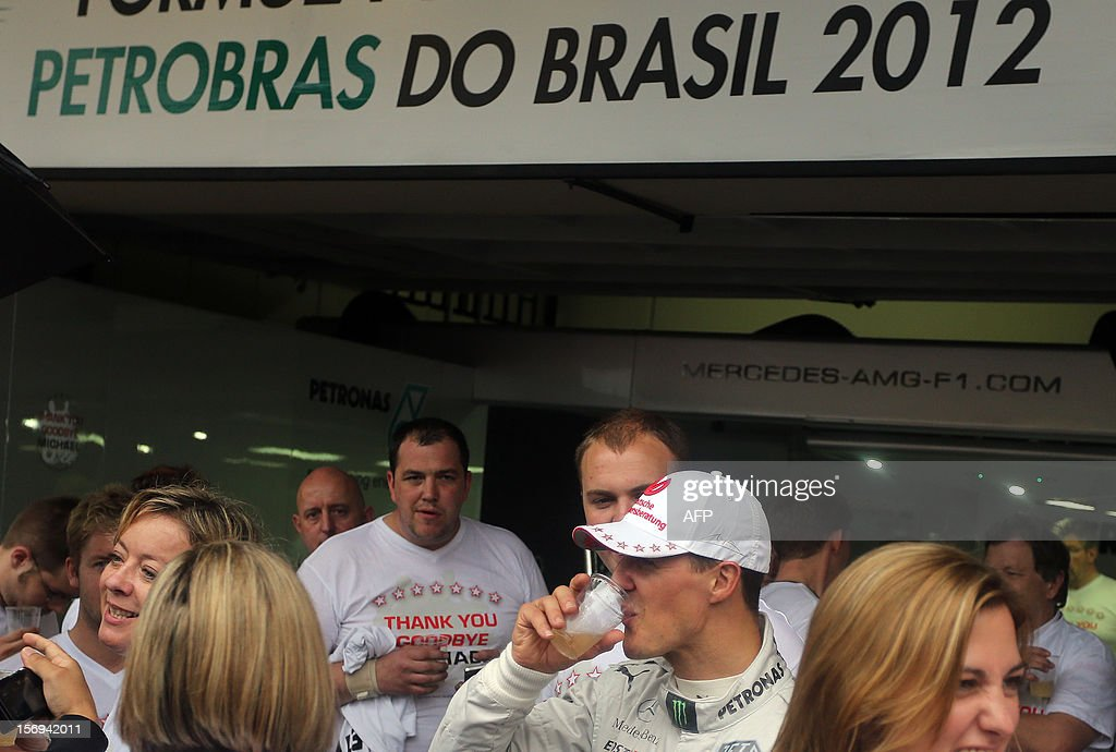 German Formula One driver Michael Schumacher enjoys a beer at the Mercedes pits at the end of the Brazil's F-1 GP on November 25, 2012 at the Interlagos racetrack in Sao Paulo, Brazil. Jenson Button won the race, followed by Fernando Alonso and Felipe Massa. AFP PHOTO