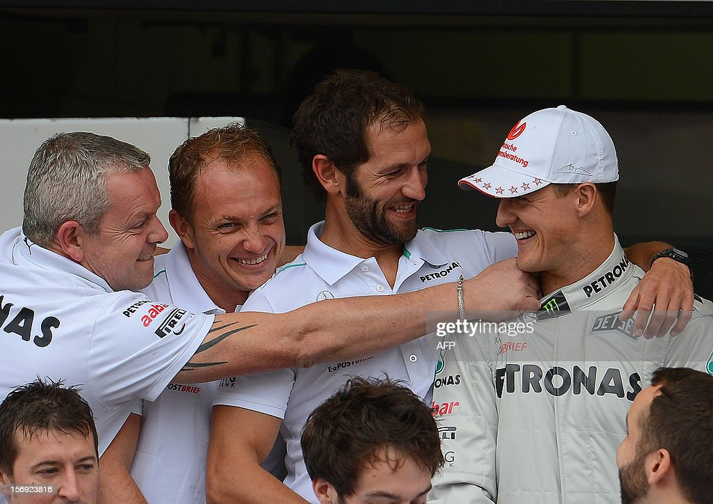 German Formula One driver Michael Schumacher (R) jokes with Mercedes team members in the pits on November 25 , 2012 at the Interlagos racetrack in Sao Paulo, Brazil. Michael Schumacher will retire from the F-1 after the Brazilian GP.