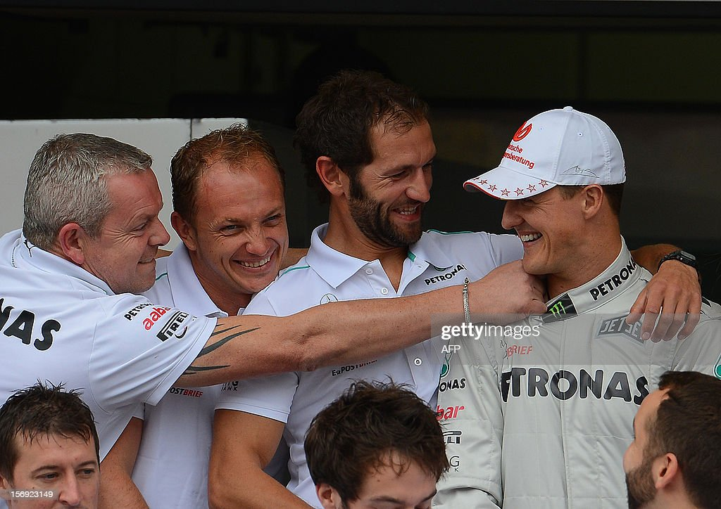 German Formula One driver Michael Schumacher jokes with the Mercedes team in the pits on November 25, 2012 at the Interlagos speedway in Sao Paulo, Brazil. Schumacher will retire from the F-1 after the Brazilain frand prix. AFP PHOTO / YASUYOSHI CHIBA / POOL
