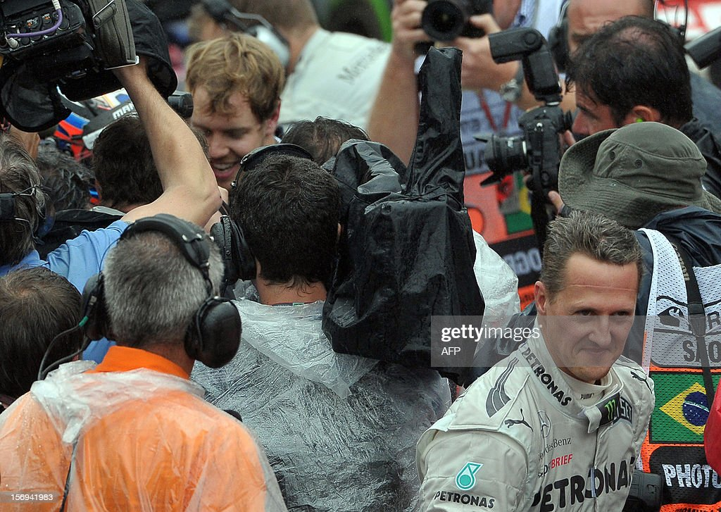 German Formula One driver Michael Schumacher (L) leaves the pits as Sebastian Vettel (back) is surrounded by journalists at the end of the Brazil's F-1 GP on November 25, 2012 at the Interlagos racetrack in Sao Paulo, Brazil. Jenson Button won the race, followed by Fernando Alonso and Felipe Massa, and Vettel arrived in sixth place, getting the F1 championship. AFP PHOTO