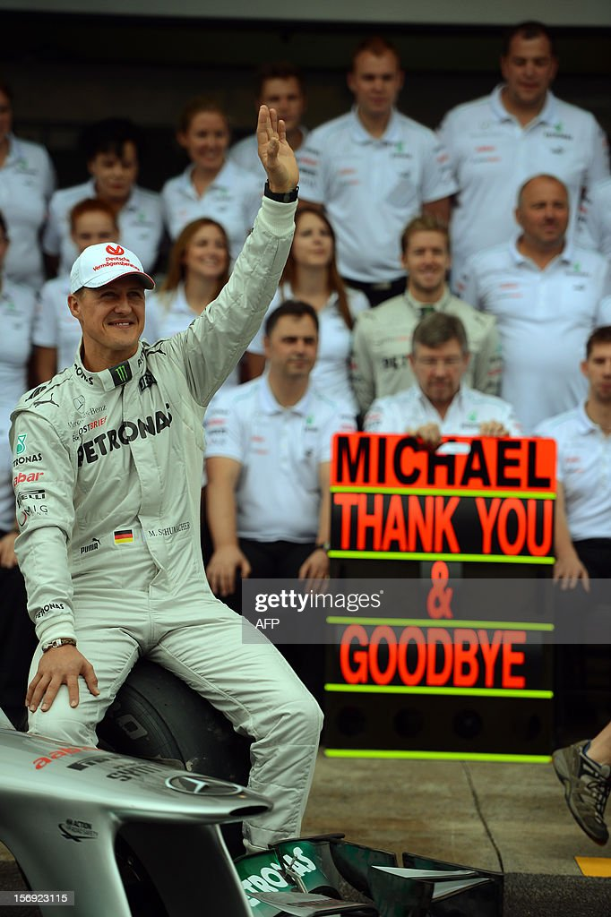 German Formula One driver Michael Schumacher poses with the Mercedes team in the pits on November 25, 2012 at the Interlagos speedway in Sao Paulo, Brazil. Schumacher will retire from the F-1 after the Brazilain frand prix. AFP PHOTO / YASUYOSHI