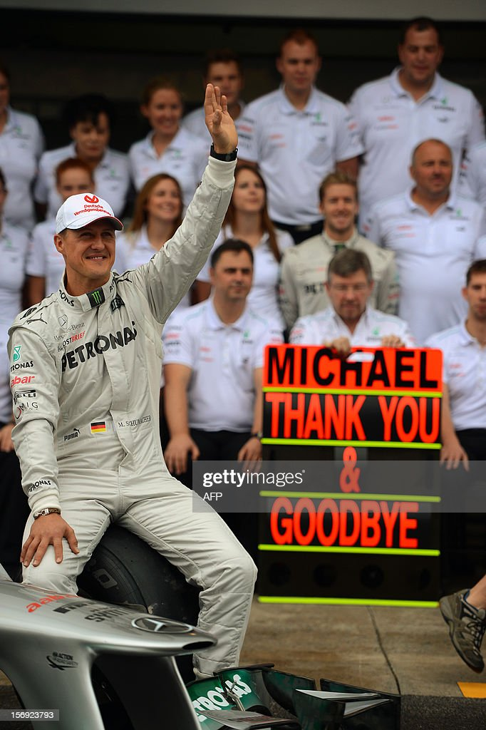 German Formula One driver Michael Schumacher poses with the Mercedes team in the pits on November 25 , 2012 at the Interlagos racetrack in Sao Paulo, Brazil. Michael Schumacher will retire from the F-1 after the Brazilian GP. AFP PHOTO/YASUYOSHI CHIBA