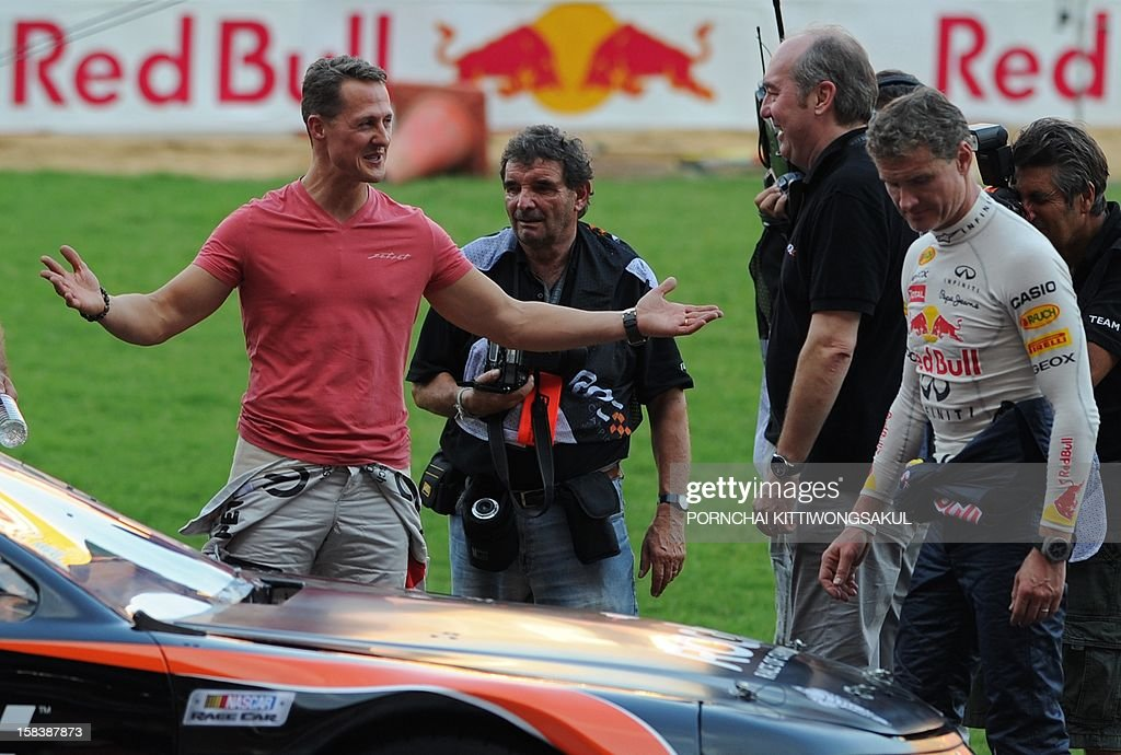 German Formula One driver Michael Schumacher (L) talks to staff members during a practice session ahead of the annual Race of Champions (ROC) at Rajamangala Stadium in Bangkok on December 15, 2012. The Race of Champions (ROC) will take place in Thailand between December 14 and 16 and brings together heavyweights from all motor racing disciplines in the same type of car. AFP PHOTO / PORNCHAI KITTIWONGSAKUL