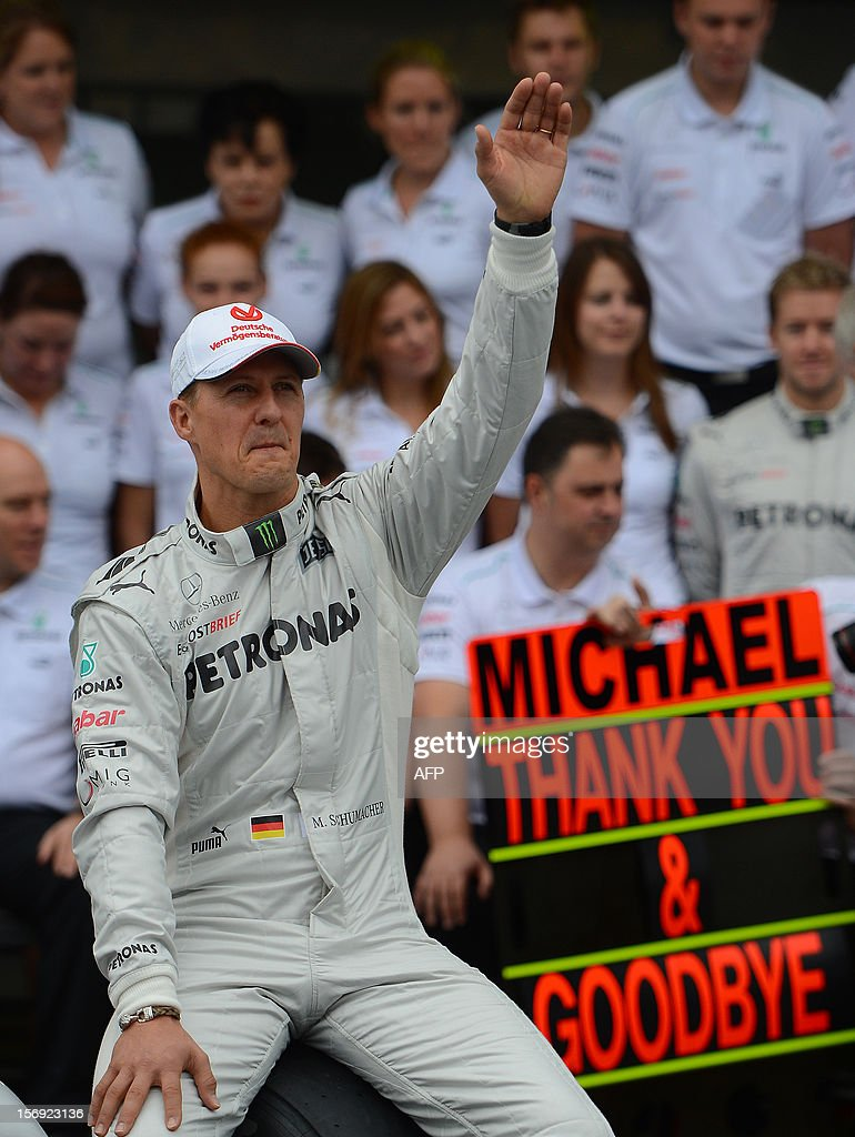German Formula One driver Michael Schumacher waves as he poses with the Mercedes team in the pits on November 25, 2012 at the Interlagos speedway in Sao Paulo, Brazil. Schumacher will retire from the F-1 after the Brazilain frand prix. AFP PHOTO / YASUYOSHI