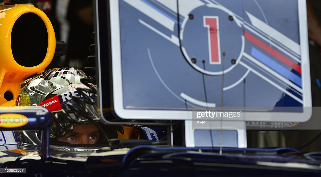 German Formula One driver Sebastian Vettel checks the lap times at the McLaren pits during the free practices for the Brazilian GP on Sunday at the Interlagos racetrack on November 22, 2012 in Sao Paulo, Brazil. AFP PHOTO YASUYOSHI CHIBA