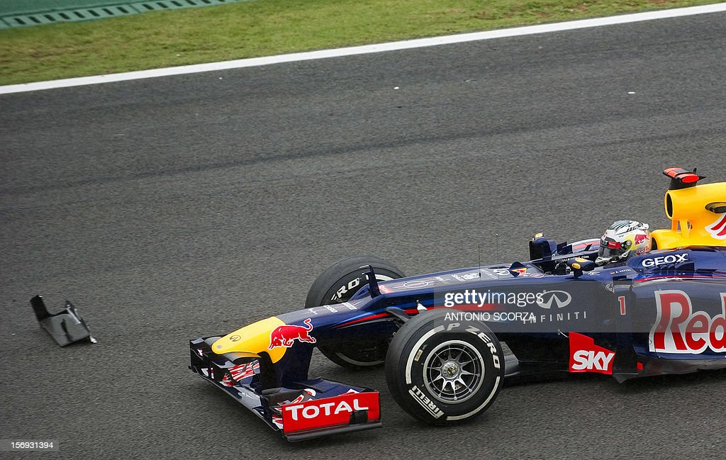 German Formula One driver Sebastian Vettel passes by a debris from a car at the S of Senna turn on November 25, 2012 during the Brazil's F-1 GP at the Interlagos racetrack in Sao Paulo, Brazil. AFP PHOTO
