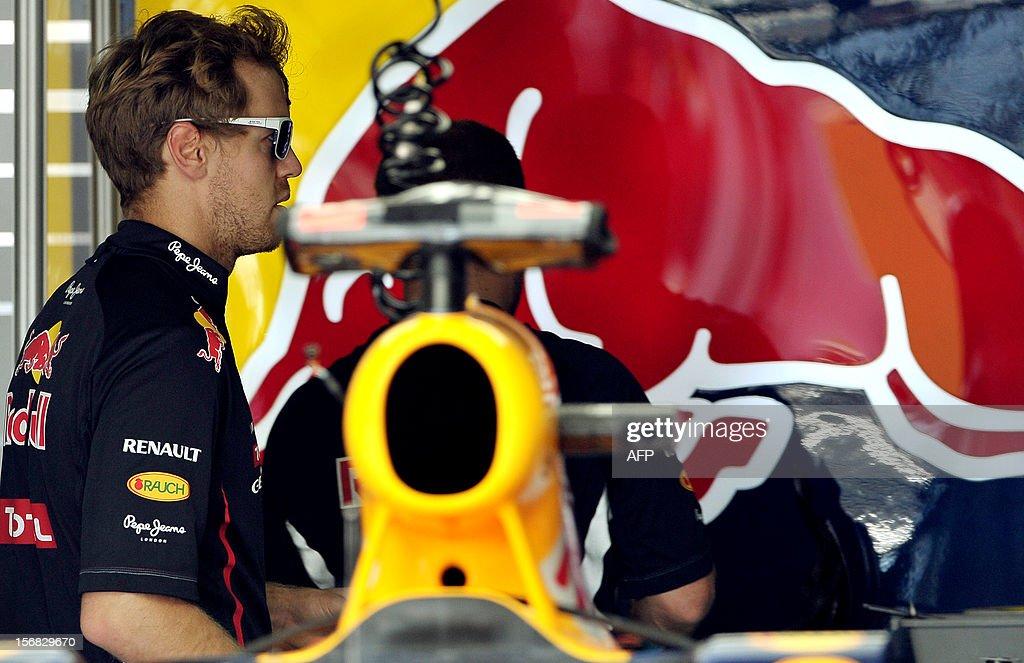 German Formula One driver Sebastian Vettel stands next to his car at Interlagos motorsport circuit in Sao Paulo on November 22, 2012 ahead of the Brazilian Grand Prix this weekend. AFP PHOTO/YASUYOSHI CHIBA