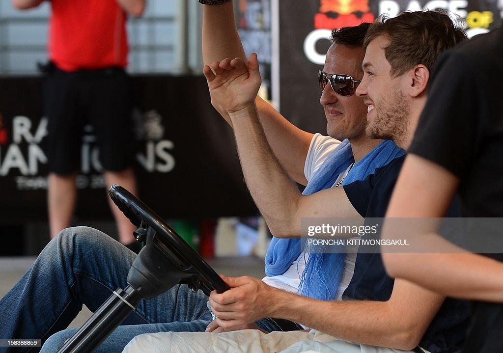 German Formula One World Champion Sebastian Vettel (R) drives a golf cart next to seven times world champion Michael Schumacher (L) of Germany during a practice session ahead of the annual Race of Champions (ROC) at Rajamangala Stadium in Bangkok on December 15, 2012. The Race of Champions (ROC) will take place in Thailand between December 14 and 16 and brings together heavyweights from all motor racing disciplines in the same type of car. AFP PHOTO / PORNCHAI KITTIWONGSAKUL