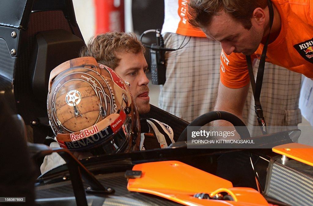 German Formula One World Champion Sebastian Vettel talks with his staff during a practice session ahead of the annual Race of Champions (ROC) at Rajamangala Stadium in Bangkok on December 15, 2012. The Race of Champions (ROC) will take place in Thailand between December 14 and 16 and brings together heavyweights from all motor racing disciplines in the same type of car. AFP PHOTO / PORNCHAI KITTIWONGSAKUL