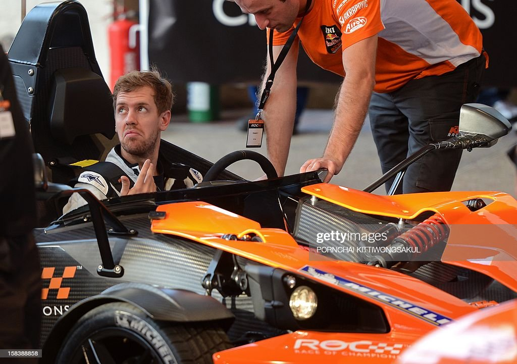 German Formula One World Champion Sebastian Vettel (L) talks with his staff members during a practice ahead of the annual Race of Champions (ROC) at Rajamangala Stadium in Bangkok on December 15, 2012. The Race of Champions (ROC) will take place in Thailand between December 14 and 16 and brings together heavyweights from all motor racing disciplines in the same type of car.