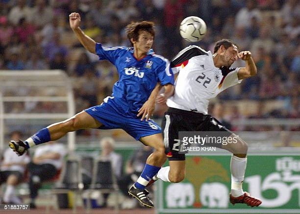 German forward Kevin Kuranyi fights for ball with Thai defender Nakarin Siriwong in the first half of a friendly match in Bangkok 21 December 2004...