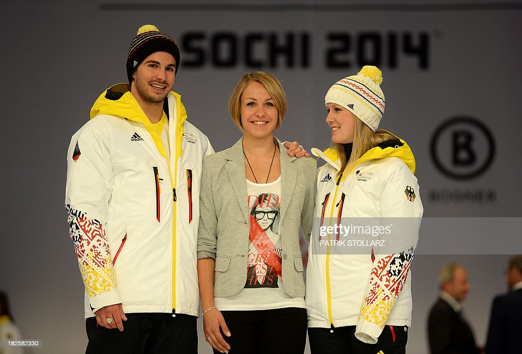 German freestyle skier Benedikt Mayer, German biathlete and former Olympic champion Magdalena Neuner and paralympic skier Andrea Rothfuss (R), present the official German olympic team's outfit for the next Olympic wintergames in Sochi, during a fashion show at the Duesseldorf fair ground, western Germany, on October 1, 2013. STOLLARZ
