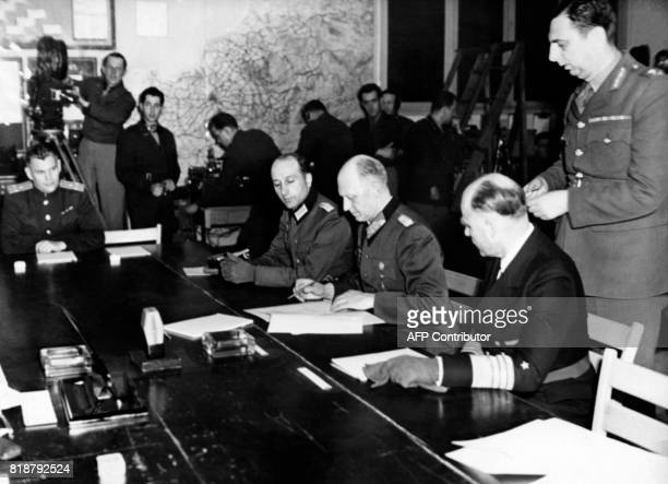 German General Alfred Jodl flanked by Admiral HansGeorg von Friedeburg and Colonel Wilhelm Oxenius signs 07 May 1945 the unconditional German...