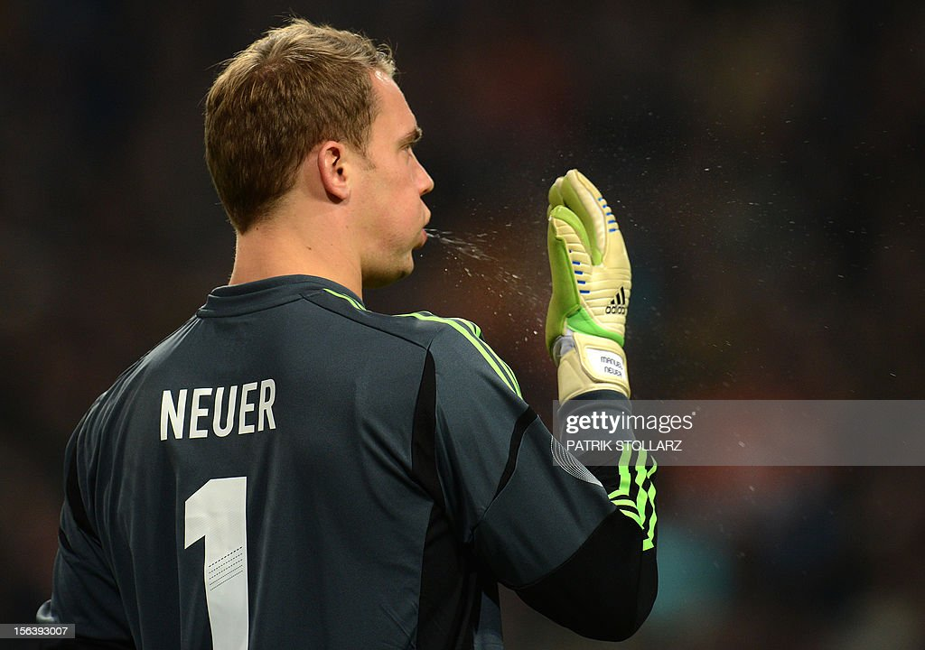 German goalkeeper Manuel Neuer spits in his glove during the friendly football match Netherlands vs Germany on November 14, 2012 in Amsterdam. AFP PHOTO / PATRIK STOLLARZ