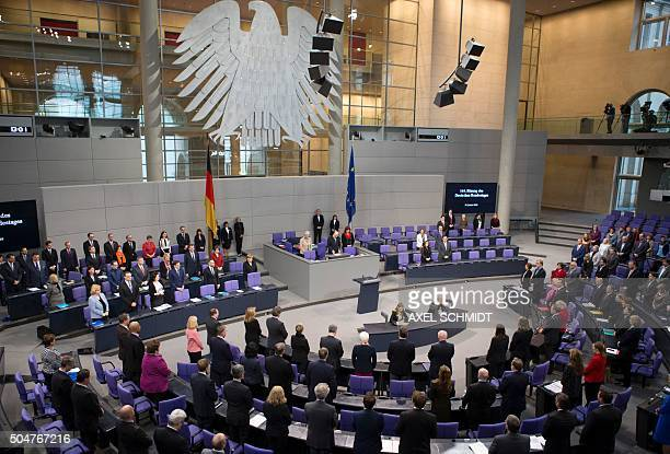 German government and parliament members stand at the opening of a plenary session at the German lower house of Parliament Bundestag on January 13...