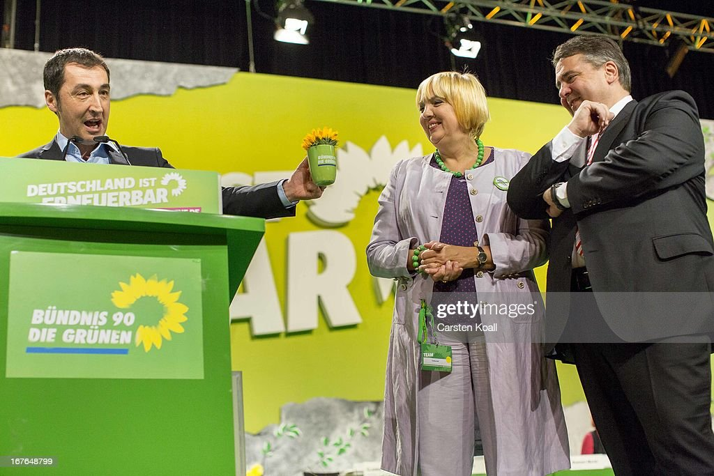German Greens Party cochairman Cem Oezdemir gives a cup to guest speaker SPD Chairman Sigmar Gabriel beside cochairwoman Claudia Roth on the second...