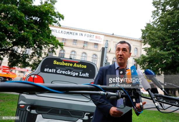 German Greens' Party coleader Cem Oezdemir gives a statement next to a placard featuring a polluting car bearing the inscription 'clean cars instead...
