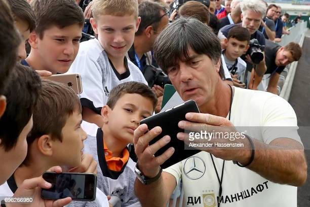 German head coach Joachim Loew takes a selfie with a fan prior to the first training session at Park Arena training ground on June 15 2017 in Sochi...