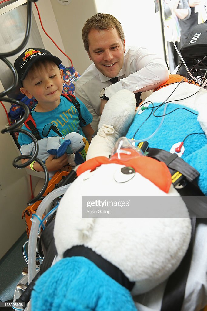 German Health Minister Daniel Bahr and Noel, 6, look on as Donald Duck, who had fictitiously fallen from a building, receives care in an ambulance at the Teddy Bear Clinic at Charite Hospital on May 8, 2013 in Berlin, Germany. Charite Hospital hosts the annual Teddy Bear Clinic days and invites children from Berlin day care centers to bring their injured teddy bears for fictitious examinations, x-rays, surgery and healing as a way for small children to become acquainted with a medical environment.