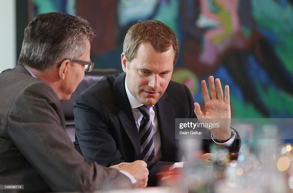 German Health Minister <a gi-track='captionPersonalityLinkClicked' href=/galleries/search?phrase=Daniel+Bahr&family=editorial&specificpeople=7622444 ng-click='$event.stopPropagation()'>Daniel Bahr</a> (R) chats with Defense Minister <a gi-track='captionPersonalityLinkClicked' href=/galleries/search?phrase=Thomas+de+Maiziere&family=editorial&specificpeople=618845 ng-click='$event.stopPropagation()'>Thomas de Maiziere</a> upon their arrival for the German government weekly cabinet meeting on May 23, 2012 in Berlin, Germany. High on the morning's agenda is a new measure aimed at curbing illegal practices among doctors and health clinics in Germany.