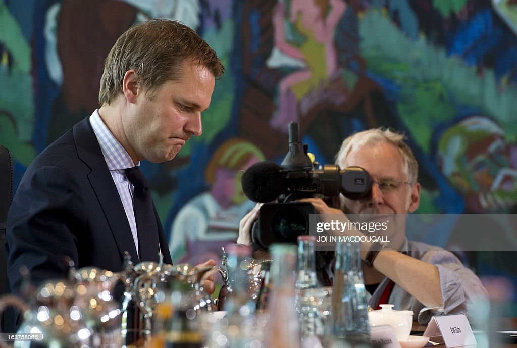 German Health Minister Daniel Bahr (L) gets some media attention as he attends a weekly cabinet meeting of the German government at the chancellery in Berlin May 15, 2013.