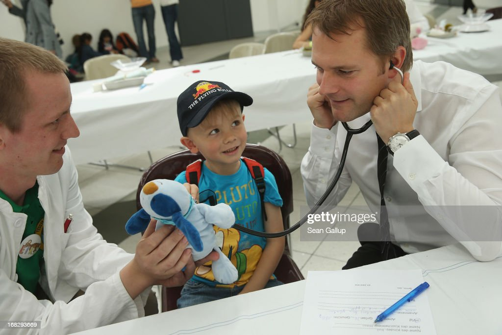 German Health Minister <a gi-track='captionPersonalityLinkClicked' href=/galleries/search?phrase=Daniel+Bahr&family=editorial&specificpeople=7622444 ng-click='$event.stopPropagation()'>Daniel Bahr</a> (R) listens for a heartbeat of Maxeis, the blue teddy creature of Noel, 6, at the Teddy Bear Clinic at Charite Hospital on May 8, 2013 in Berlin, Germany. Charite Hospital hosts the annual Teddy Bear Clinic days and invites children from Berlin day care centers to bring their injured teddy bears for fictitious examinations, x-rays, surgery and healing as a way for small children to become acquainted with a medical environment.