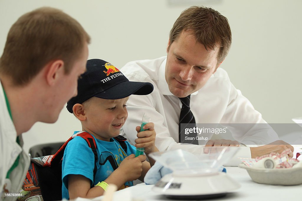 German Health Minister <a gi-track='captionPersonalityLinkClicked' href=/galleries/search?phrase=Daniel+Bahr&family=editorial&specificpeople=7622444 ng-click='$event.stopPropagation()'>Daniel Bahr</a> (R) looks on as Noel, 6, prepares to give his blue teddy creature a fictitious injection at the Teddy Bear Clinic at Charite Hospital on May 8, 2013 in Berlin, Germany. Charite Hospital hosts the annual Teddy Bear Clinic days and invites children from Berlin day care centers to bring their injured teddy bears for fictitious examinations, x-rays, surgery and healing as a way for small children to become acquainted with a medical environment.
