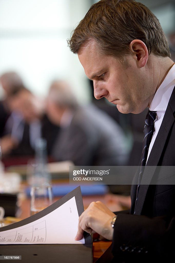 German health minister Daniel Bahr reads his brief during the weekly cabinet meeting at the Chancellery in Berlin on February 27, 2013. AFP PHOTO / ODD ANDERSEN