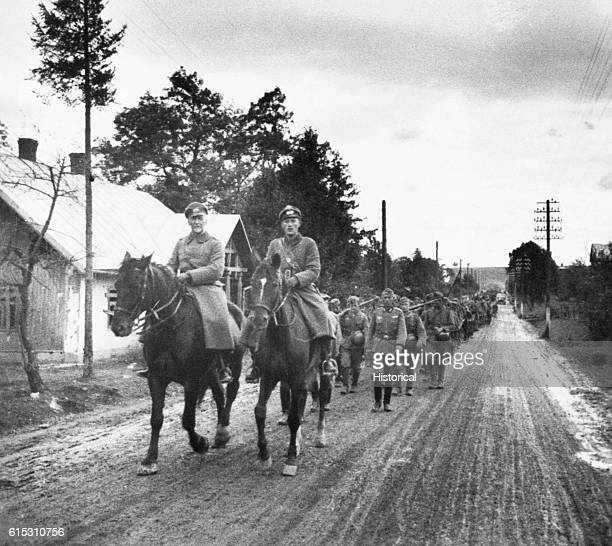German Infantry reserves march to the Front down a dirt road through DobromilPrzemysl Poland They are led by two officers on horseback | Location...