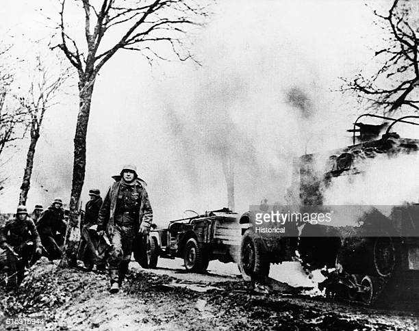 German infantry walk past burning Allied vehicles somewhere in Belgium during the Battle of the Bulge December 1944