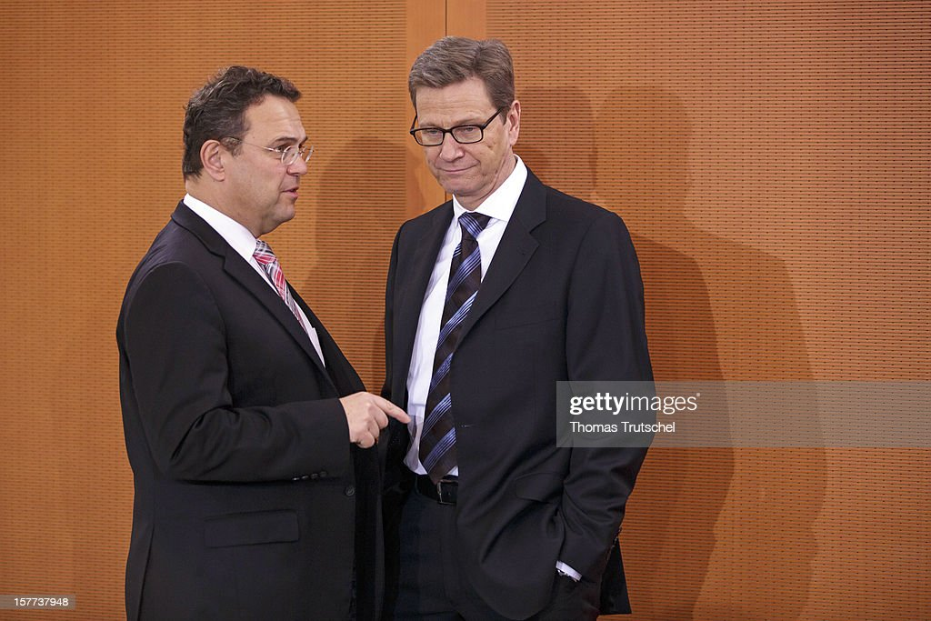German Interior Minister Hans-Peter Friedrich (L) and German Foreign Minister Guido Westerwelle talk at the arrival for the weekly German government cabinet meeting on December 6, 2012 in Berlin, Germany.