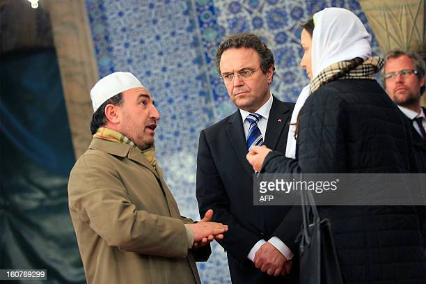 German interior minister HansPeter Friedrich and Turkish Imam Ismail Karakelle speak with an unidentified woman during a visit to the Rustem Pasha...